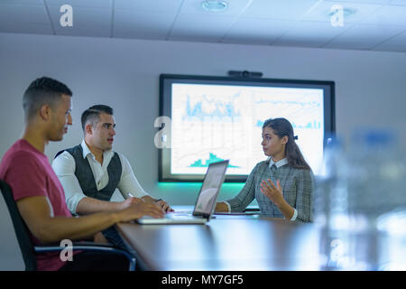 Business team using laptop and interactive screens with charts and graphs in business meeting - Stock Photo