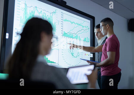 Business team viewing charts and graphs on interactive screen in business meeting - Stock Photo