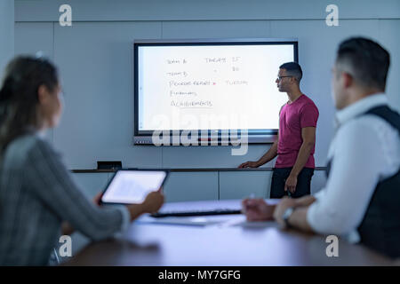 Businessman writing on interactive screen in business meeting - Stock Photo
