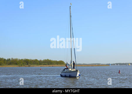 Yacht approaching mooring on Hickling Broad, Norfolk - Stock Photo