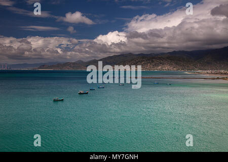 Bay, dark clouds over the mountains, South China Sea, near Vinh Hy, Ninh Thuan, Vietnam - Stock Photo