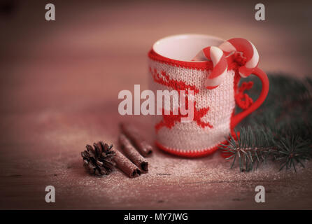 Christmas Cup ornaments and cinnamon sticks on wooden background - Stock Photo
