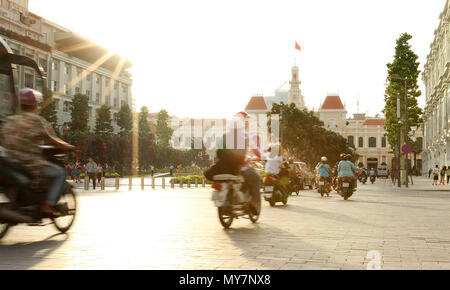 View to Ho Chi Minh city town hall on sunset with motorbikes moving and Vietnamese flag flying. Tourist travel holiday guide concept. Vietnam - Stock Photo