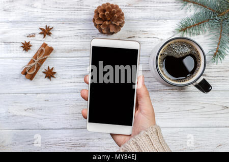Girl holding white smartphone in hand on white wooden desk surrounded with coffee and christmas decoration. - Stock Photo