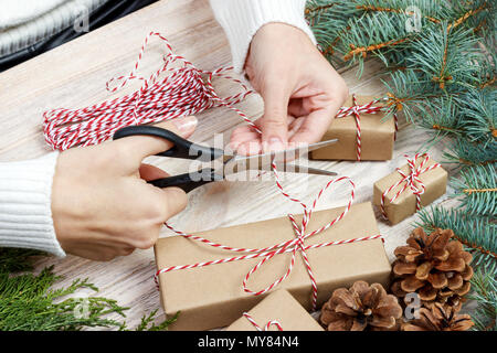 Christmas gift wrapping background. Female hands packaging christmas present with red ribbon, top view. Winter holidays concept, flat lay. Woman holdi - Stock Photo