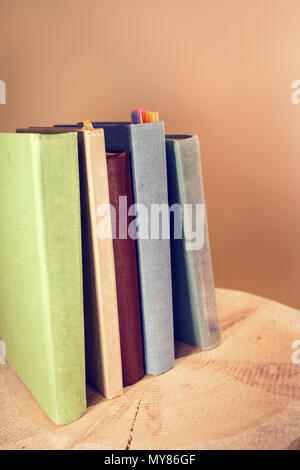 Retro toned image of vertical stack of old books on wooden saw cut. - Stock Photo