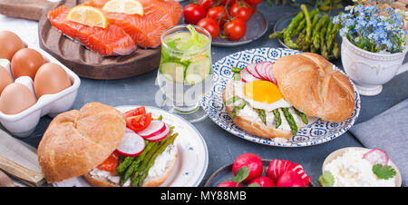 Bread with cheese, egg and asparagus, another bread with salmon and. asparagus. Healthy food. Tasty breakfast. Gray background. Banner, copy space - Stock Photo