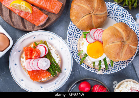 Bread with cheese, egg and asparagus, another bread with salmon and. asparagus. Healthy food. Tasty breakfast. Gray background. Flat lay - Stock Photo