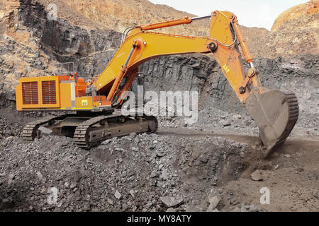 Excavator digging out ore rich rock and loading it onto rock dump trucks for processing - Stock Photo