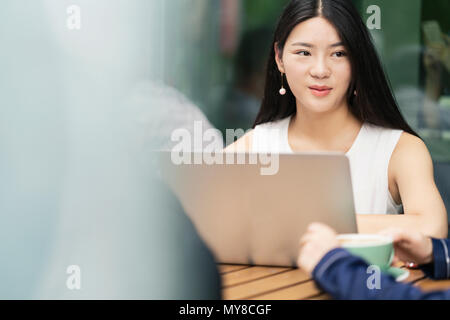 Group of businesspeople, having meeting at cafe, using laptop