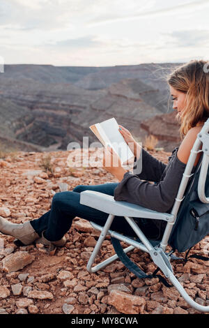 Young woman in remote setting, sitting on camping chair, reading book, Mexican Hat, Utah, USA - Stock Photo