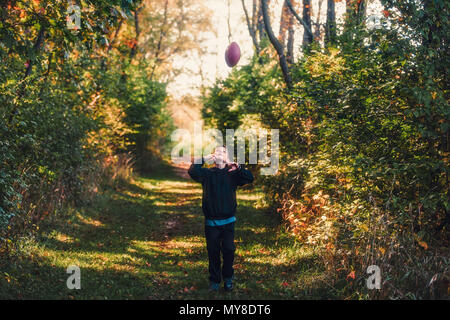 Young boy in rural setting, throwing american football in air - Stock Photo
