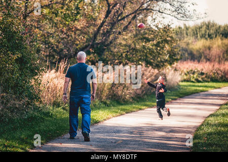 Father and son playing with ball on pathway - Stock Photo