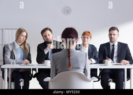 Woman during job interview and four elegant members of management - Stock Photo