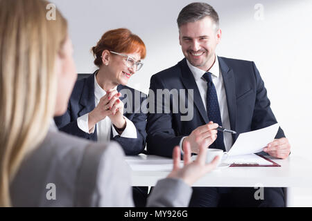 Job applicant back view and two elegant corporate workers - Stock Photo