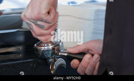 Barista presses ground coffee using tamper - Stock Photo