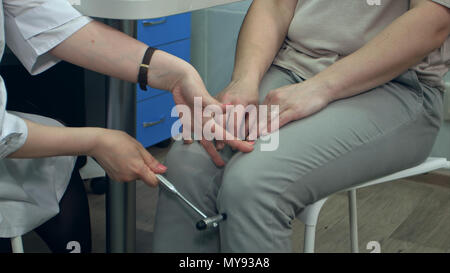 Neurologist testing reflexes on female patient using hammer - Stock Photo