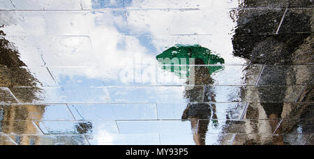 Blurry reflection shadow silhouettes of people walking on a rainy pedestrian street  in summer - Stock Photo
