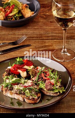 Italian sandwiches - bruschetta with meat pate, arugula, sun dried tomato and seeds on bread on dark wooden table. - Stock Photo