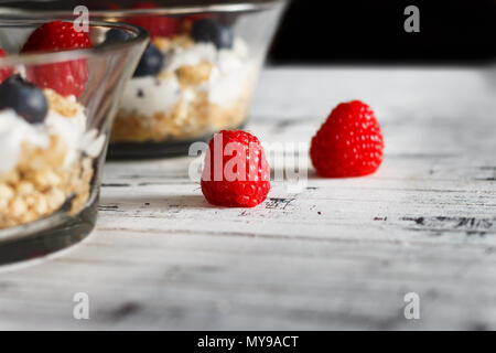 Raspberries, blueberries, cereals and yogurt in a glass bowl on wooden slats. Healthy breakfast for a healthy life. Horizontal image. - Stock Photo