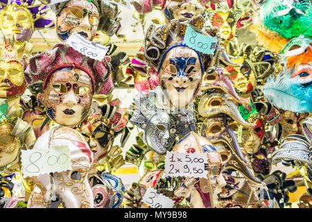 Carnival masks put on sale in a street market in Florence. - Stock Photo