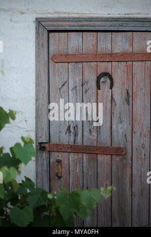 Horseshoe hangs on the old door - a symbol of happiness or a guard against evil forces - Stock Photo