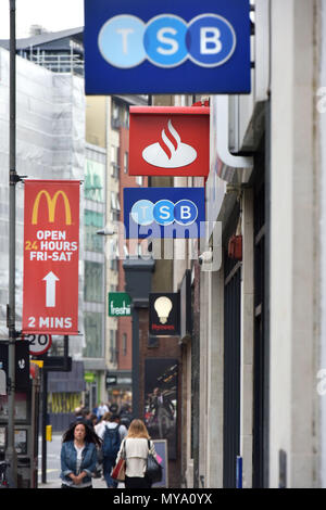 People walk past the bank branches of the TSB and Santander banks, Holborn, central London, with a McDonald's promotional poster in the background. - Stock Photo