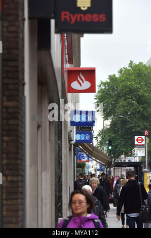 People walk past the bank branches of the TSB, Santander and Nationwide banks, Holborn, central London, with a bus stop in the background. - Stock Photo