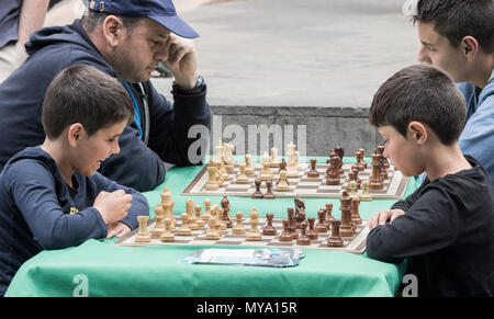 Children playing chess outdoors in Spain - Stock Photo