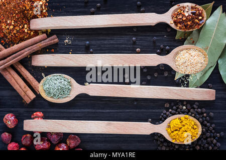 Four wooden spoons with various spices on dark wooden background - Stock Photo