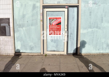 The shadows of people walking past the closed branch of the bank Santander on Kentish Town Road. Banks are closing more branches on the high street as - Stock Photo