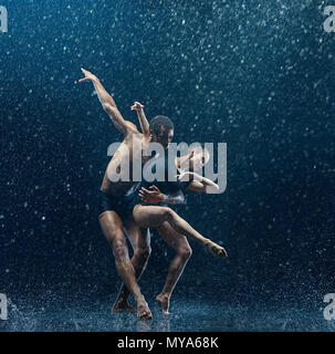 Young couple of ballet dancers dancing under water drops - Stock Photo
