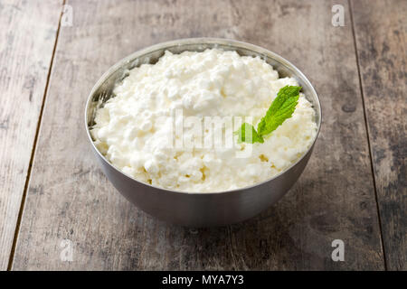 Fresh cottage cheese in a metal bowl on wooden table - Stock Photo