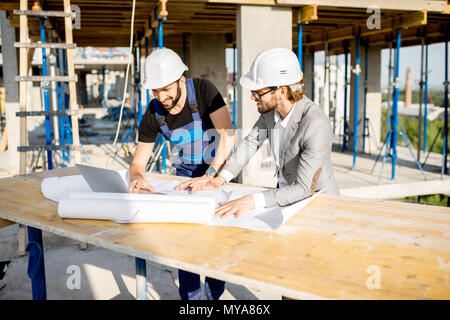 Engineer with worker at the construction site - Stock Photo