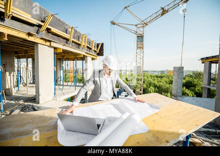 Engineer with drawings on the structure - Stock Photo