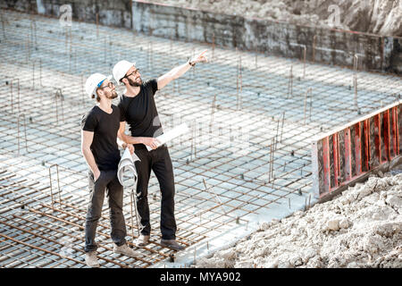 Builders with drawings at the construction site - Stock Photo