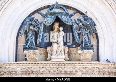 Detail of the facade of the cathedral of Orvieto, Umbria, Italy. Marble statue of the Virgin Mary with bronze angels - Stock Photo