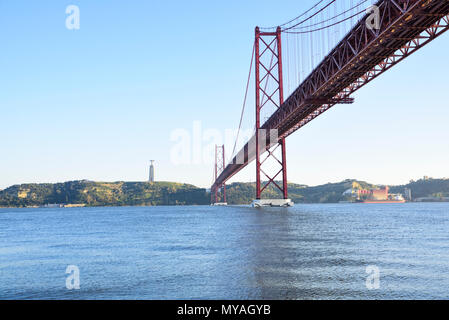 the famous bridge 25 April on the river Tagus in Lisbon Inspired by the golden gate of San Francisco. In the background the statue of Cristo Rei - Stock Photo