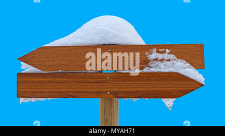 Direction sign signpost snow covered in winter, isolated on blue background, arrows pointing left and right, easy object selection wiith one click on  - Stock Photo