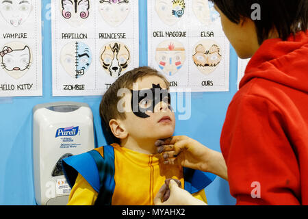 A woman doing a young boy (6 yrs old) face painting as Batman at a children's party - Stock Photo