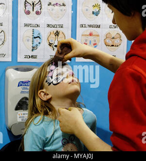 A woman face painting a little girl (3 yr old) as Hello Kitty at a children's party - Stock Photo