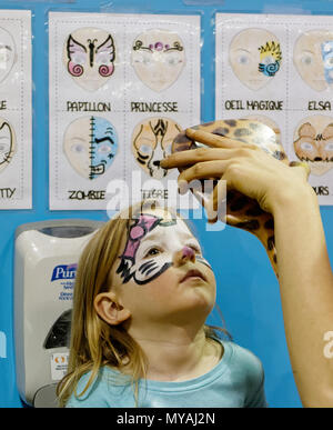 A young girl (3 yr old) admiring her new Hello Kitty face paint in a mirror - Stock Photo