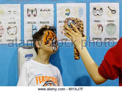 A young boy (6 yr old) admiring his new tiger face paint in a mirror - Stock Photo