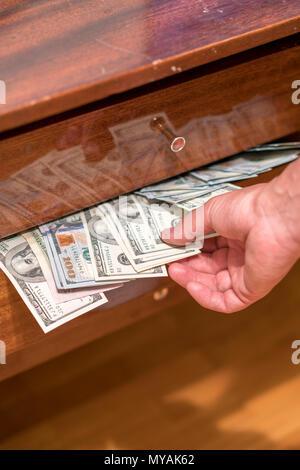 The hand taking dollars from the desk drawer. One hundred bills in desk drawer. - Stock Photo