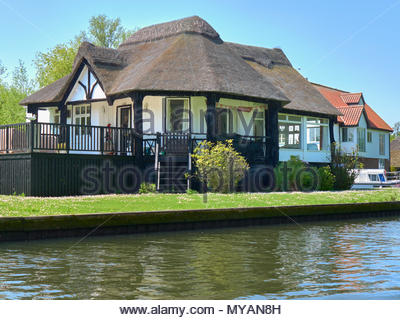 A riverside cottage with a thatched roof in the norfolk broads national park in england uk - Stock Photo