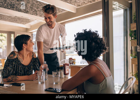 Male waiter serving water to women at cafe. Female friends at a restaurant with waiter serving water. - Stock Photo