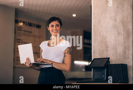 Smiling caucasian woman standing in her coffee shop with a laptop. Female manager with laptop in a restaurant. - Stock Photo