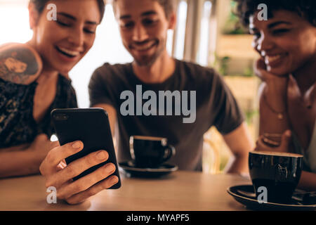 Friends having fun using a smart phone in cafe. Focus on mobile phone of a man with female friends sitting by and smiling. - Stock Photo