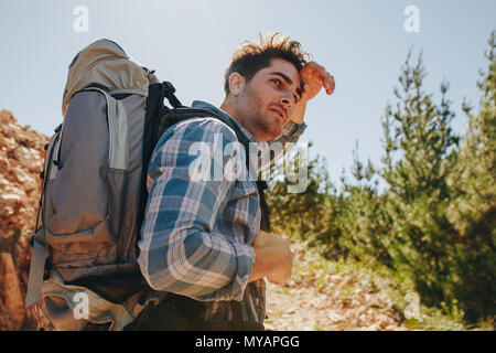 Male hiker trekking on mountains. Young man exploring nature walking through mountain trails. - Stock Photo