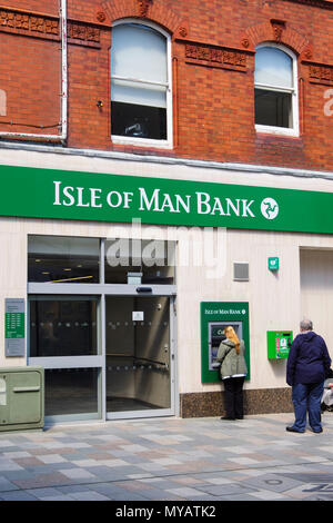 People using a cashpoint ATM outside Isle of Man Bank branch in Douglas, Isle of Man, British Isles - Stock Photo